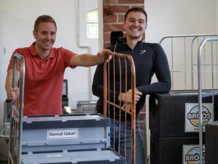Maarten und Beerend stehen lächelnd im Lager